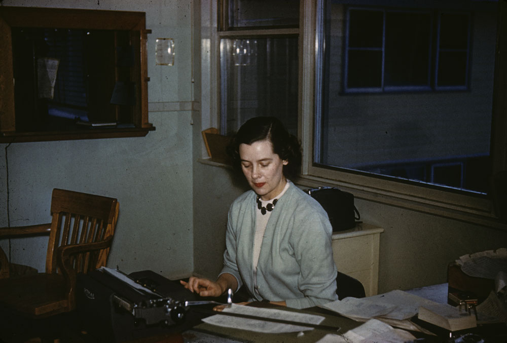Woman seated at desk, typing document on a typewriter. (item 1)