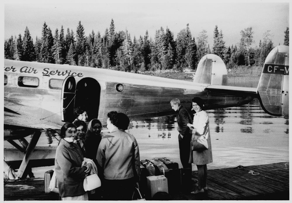 Community Aides leaving Moose Factory on a small Hooker Air Service aircraft. (item 1)