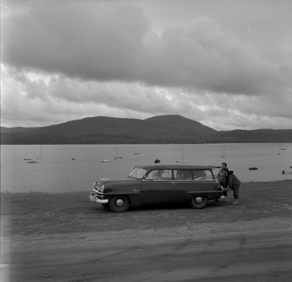 Photo of three women standing outside a station wagon, with a river and distant hills in the background.