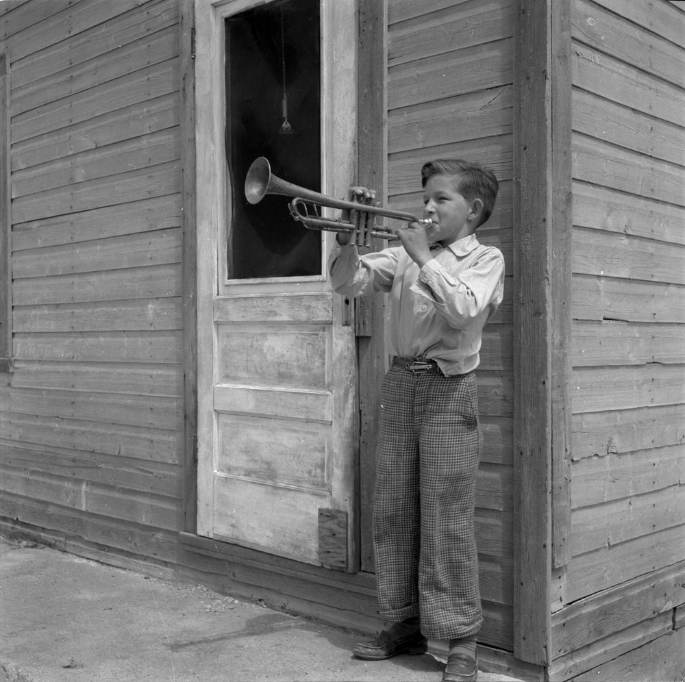 Black and white photograph of a young boy standing in front of a building and playing a trumpet.