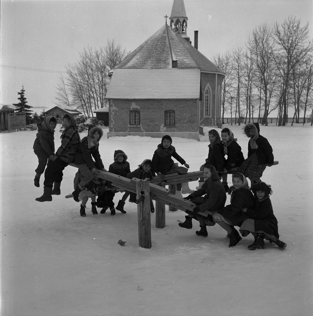 Black and white photograph of fourteen children, all dressed in winter clothing, playing on two wooden seesaws in a snowy field with a church, two other small buildings, trees, and a fence in the background.