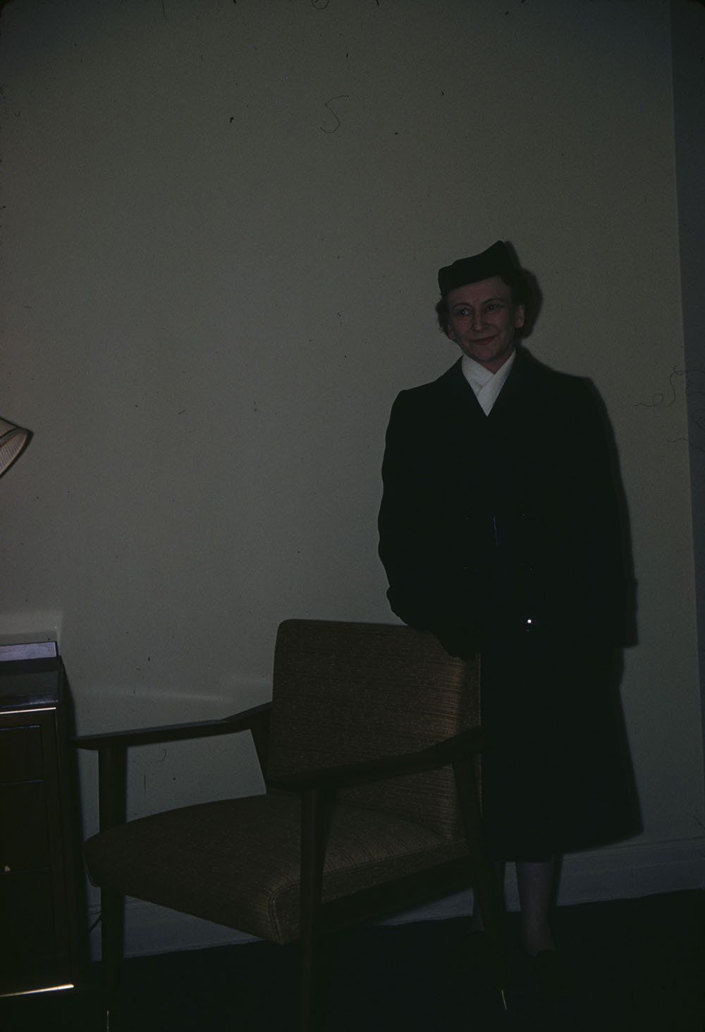 A.K. Smith in new uniform standing beside desk chair. (item 1)