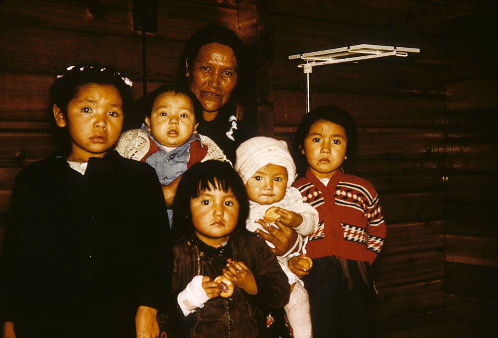 Aboriginal woman standing with group of children in log house, Little Grand Rapids. (item 1)