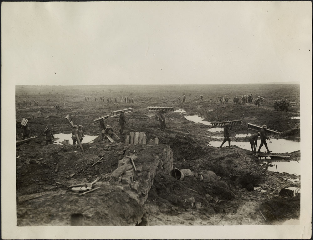 Canadian Pioneers carrying trench mats with wounded and prisoners in background during the Battle of Passchendaele. (item 2)