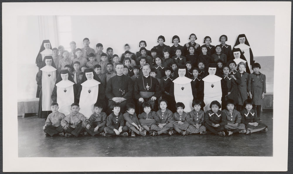 Cross Lake Indian Residential School, class portrait of students, priests and nuns, February 1940