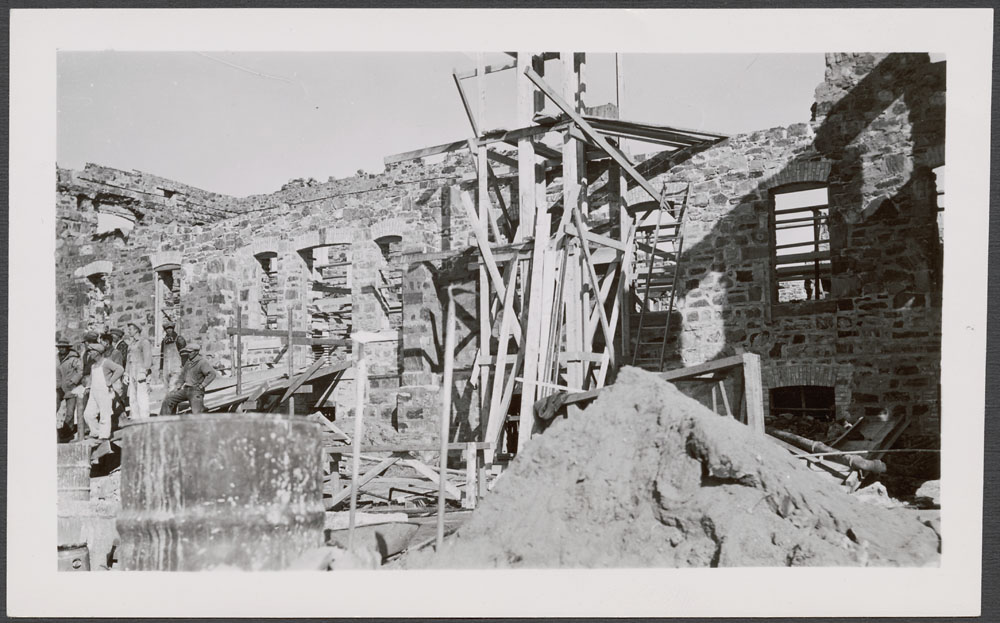 Cross Lake Indian Residential School, view of a partially constructed wall with scaffolding and workers, October 1938