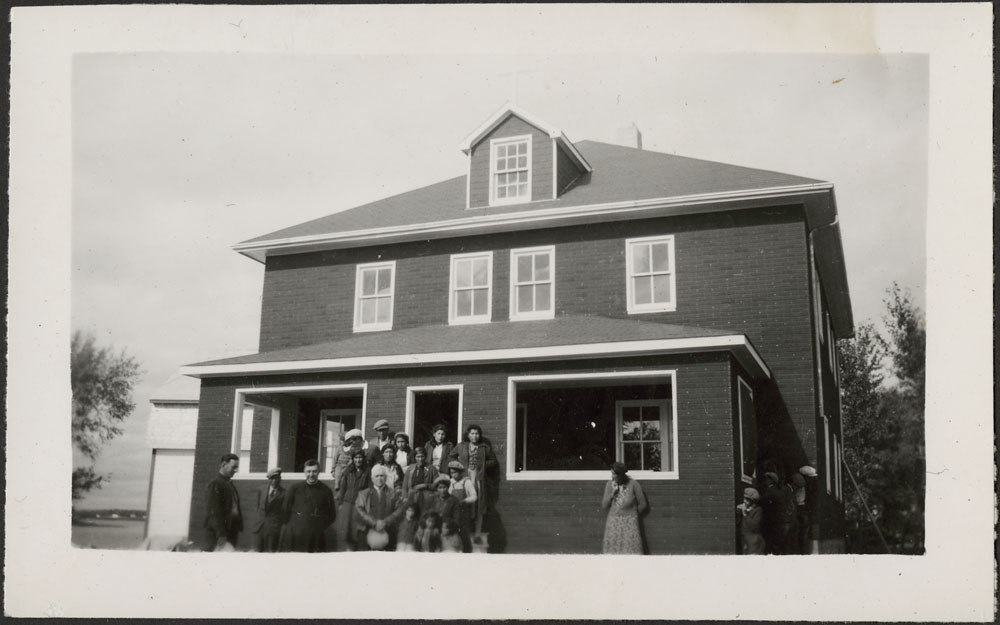 Cross Lake Indian Residential School,  group of Cree students with a priest and other adults in front of the new Oblate residence, September 1944