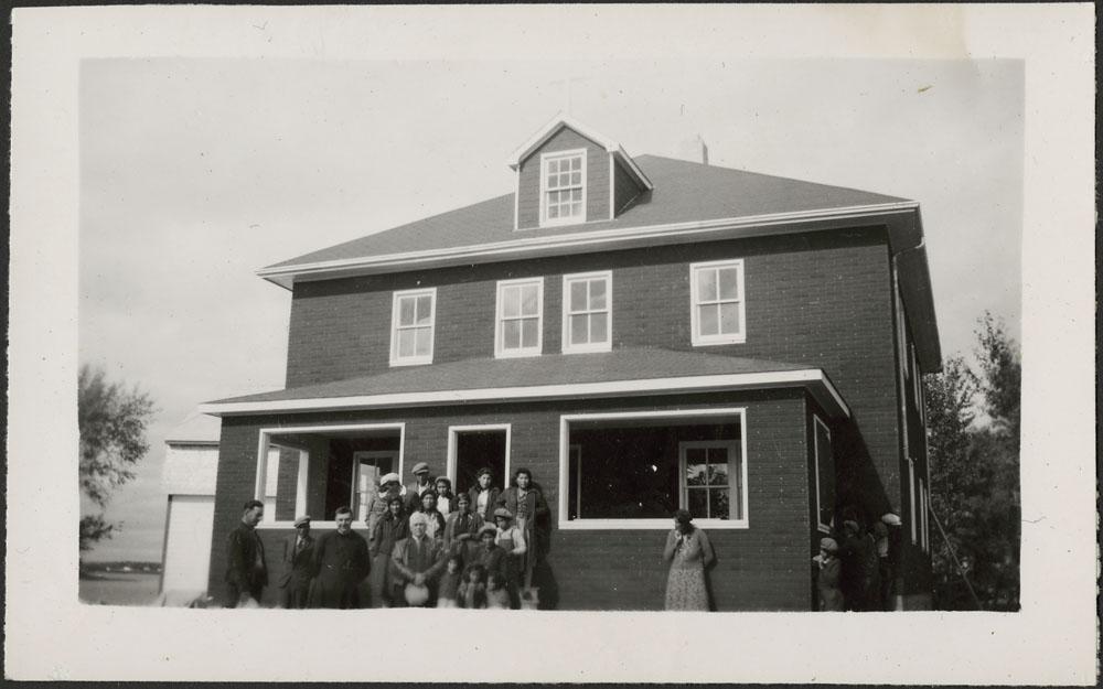 Pensionnat indien de Cross Lake, groupe d'élèves cris avec un prêtre et d'autres adultes devant la nouvelle résidence des Oblats, septembre 1944