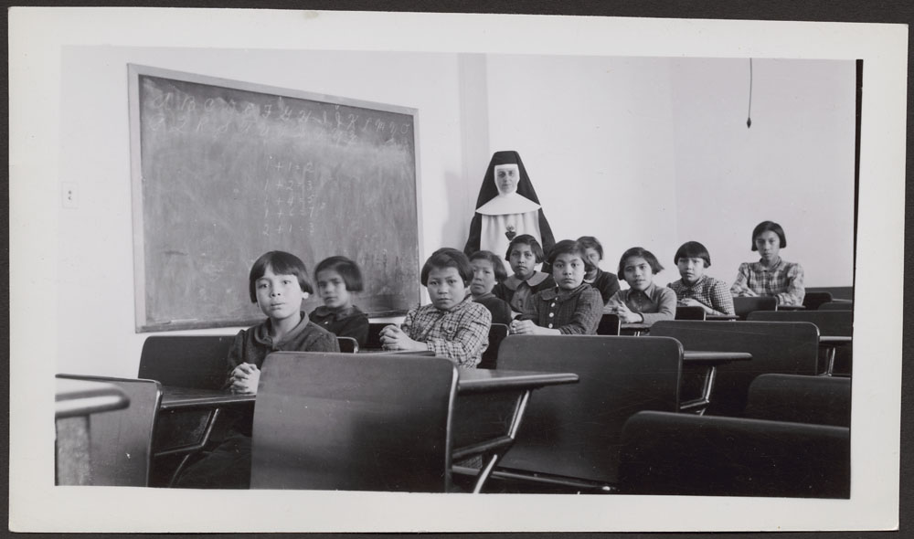 Cross Lake Indian Residential School, female students and a nun in a classroom, February 1940