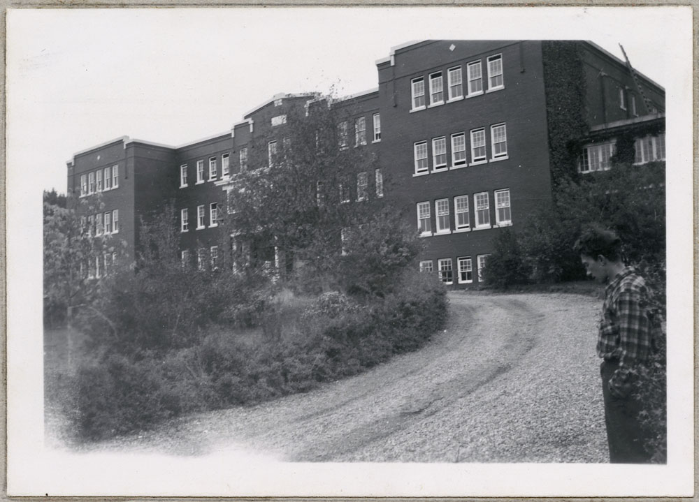 St. Michael's Indian Residential School (Alert Bay), view from the driveway with a male student in the foreground, 1949