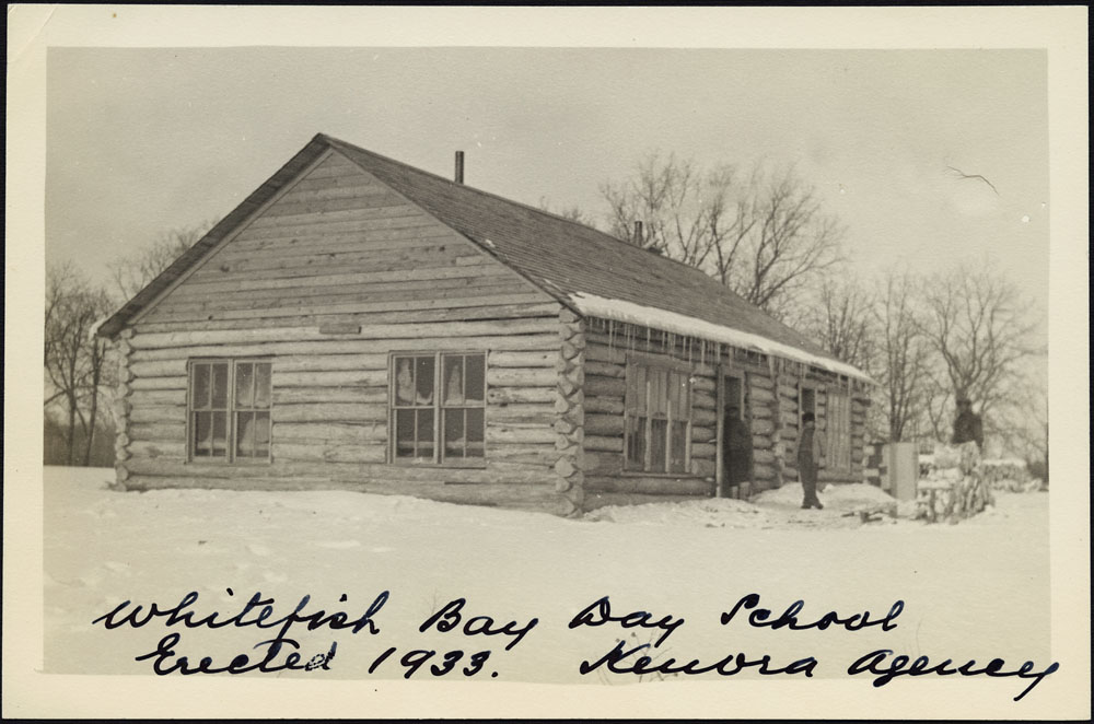 Whitefish Bay Indian Day School, corner view of the school with three men standing near the entrance, Whitefish Bay, 1941