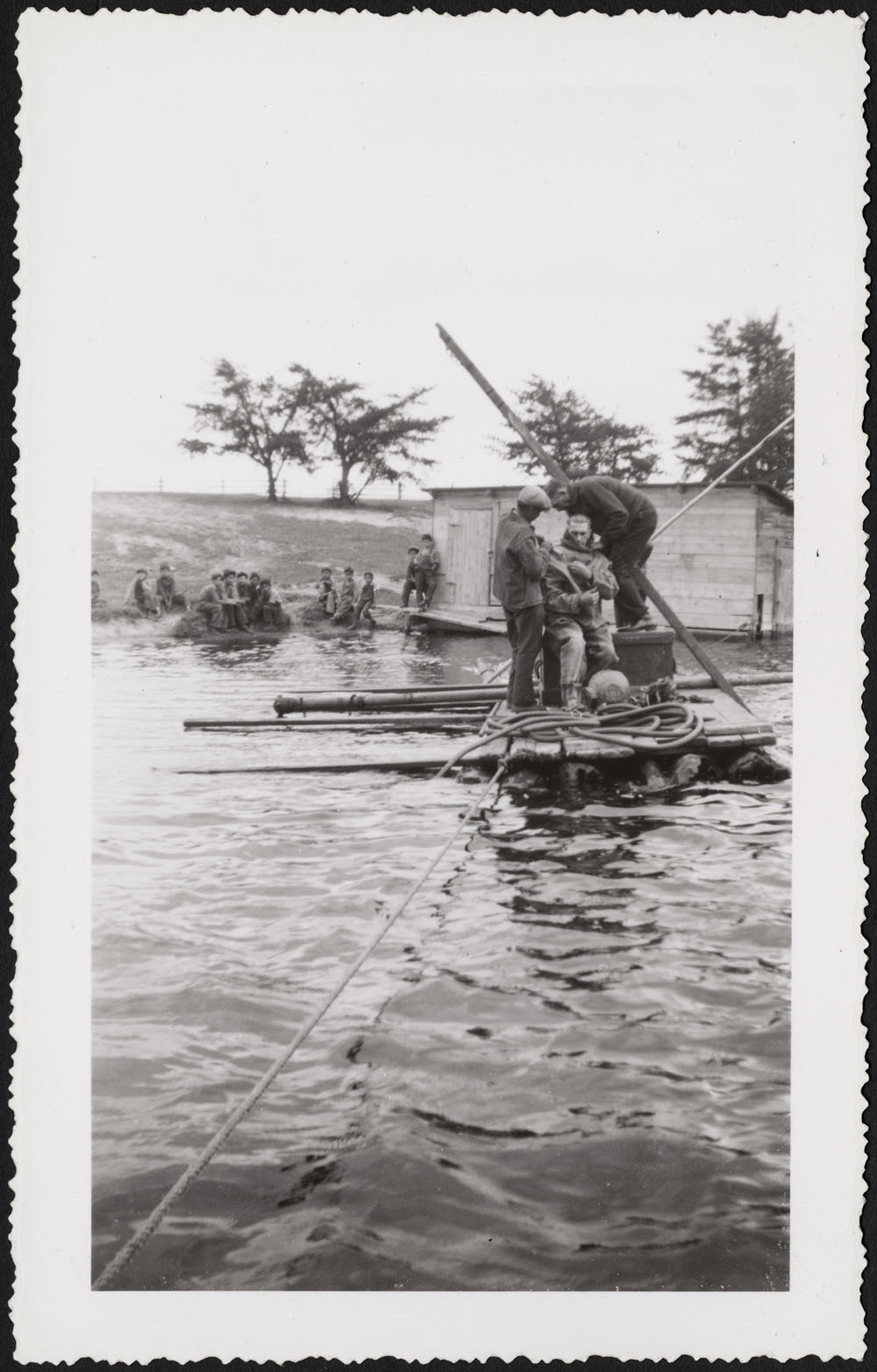Saint John's Indian Residential School, a diver preparing to repair intake of water supply system as students watch from boathouse and shore, Chapleau, week of October 23, 1933
