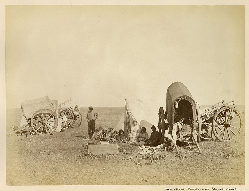 Black and white photograph of eleven people, ten seated and one standing, on a flat, grassy landscape with two tents and four two-wheeled carts.