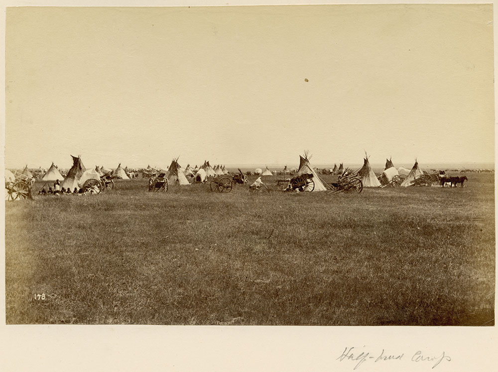 Black and white photograph of numerous teepees and two-wheeled carts on the plains with a small group of people sitting near a teepee on the left side of the composition.