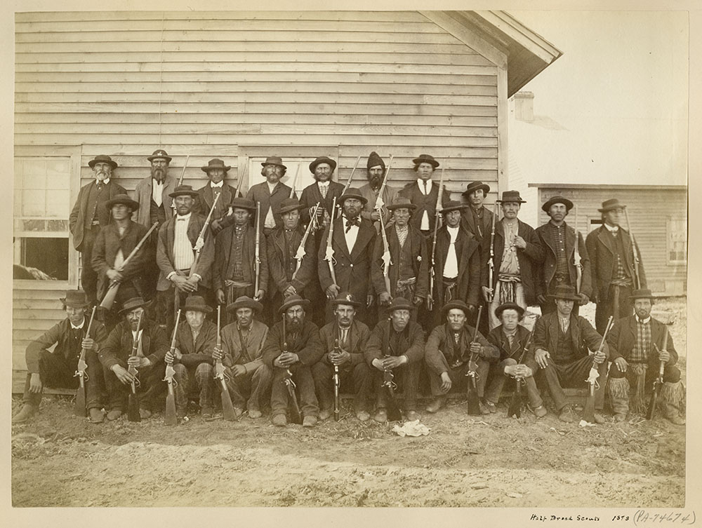 Black and white photograph of twenty-nine men holding rifles and posing in three rows in front of a building.