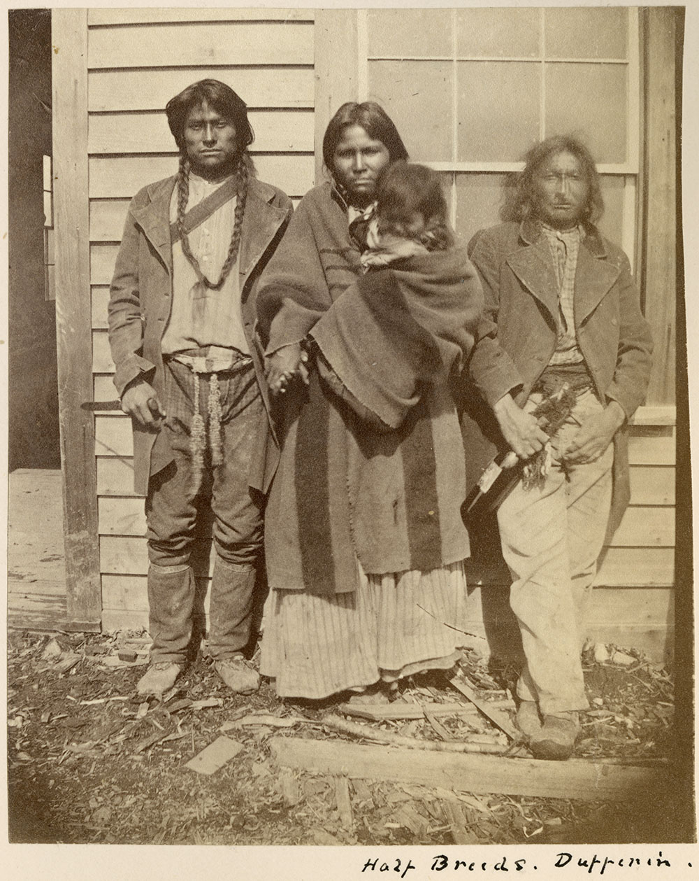 Black and white photograph of two men and a woman holding a child posed in front of a wooden building.