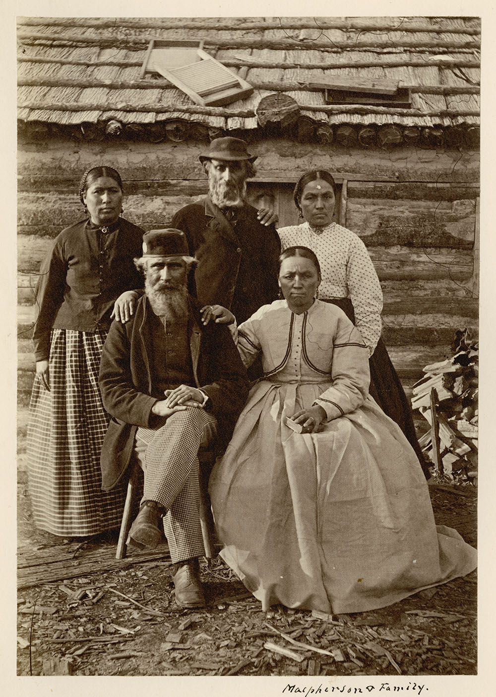Black and white photograph of one man and one women sitting down with three other figures standing behind them in front of a wooden building.