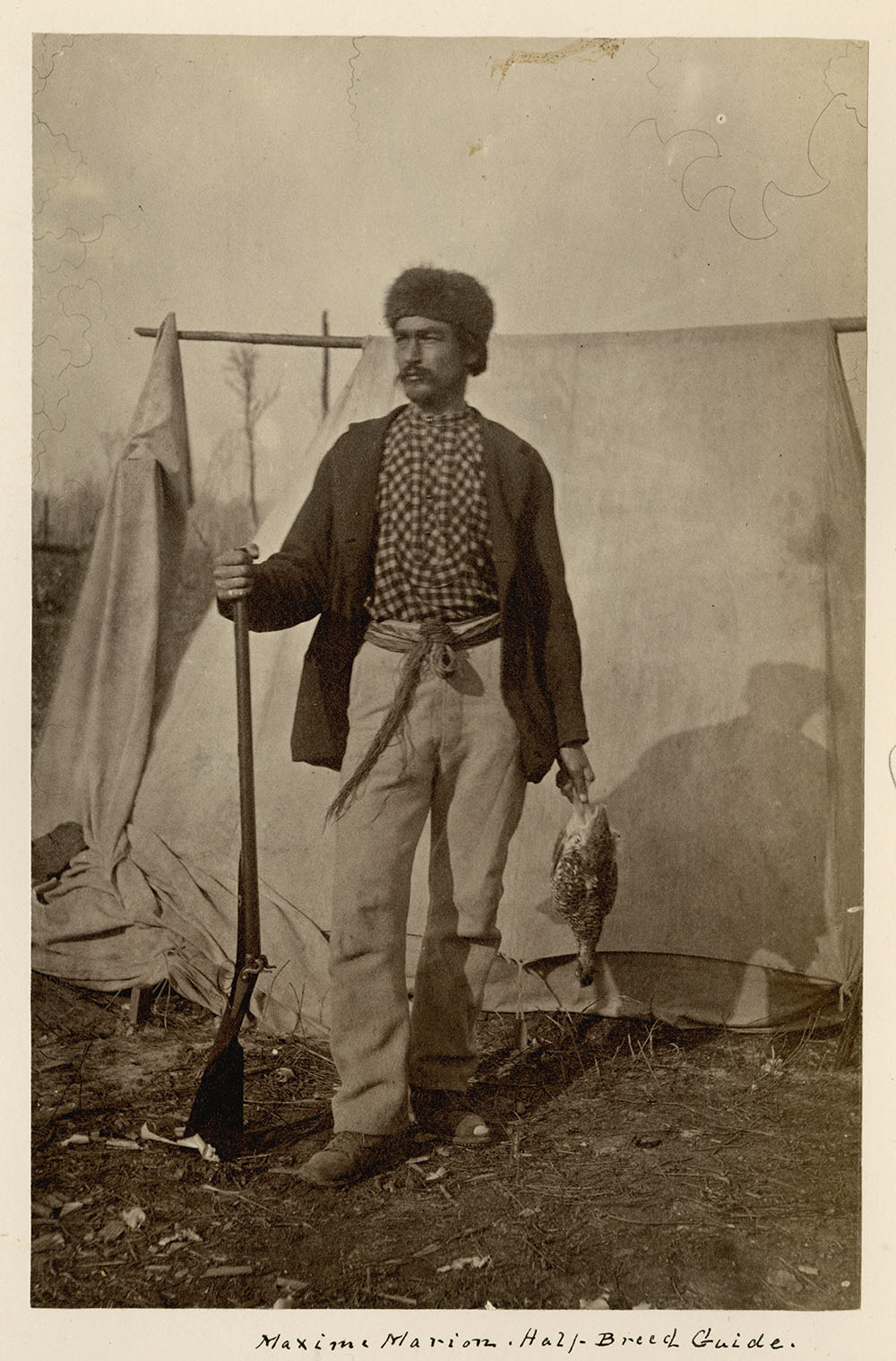 Black and white photograph of a man wearing a fur cap and a plaid shirt under a dark coloured jacket standing outside in front of a tent while holding a rifle and a dead grouse.