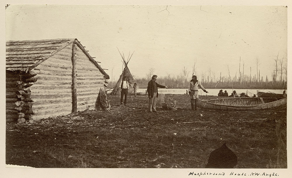 Black and white photograph of a log house with two men in the yard pointing at a canoe on the ground; several other men,  a teepee, and a body of water with trees are in the background.