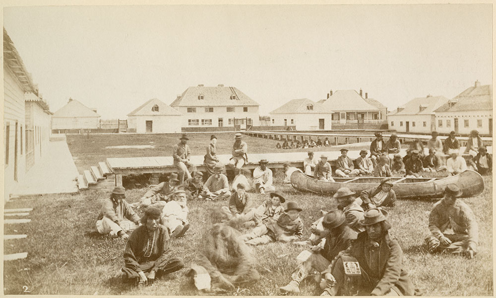 Black and white photograph of a group of about thirty-five men and women sitting with a canoe on a lawn surrounded  by eight buildings.