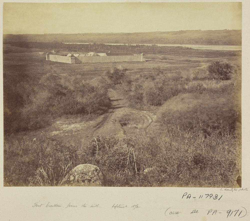 Black and white photograph taken at a distance of a fort surrounded by walls built on a grassy plain next to a river.