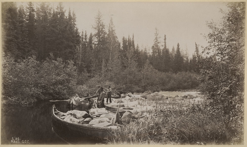 Black and white photograph of six men standing with canoes packed with supplies on a river lined on both sides with trees.