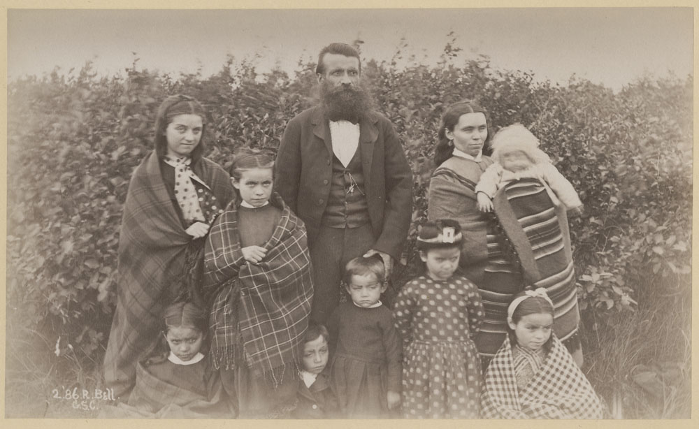 Black and white photograph of a man and a woman along with eight children of various ages standing in front of a large hedge.