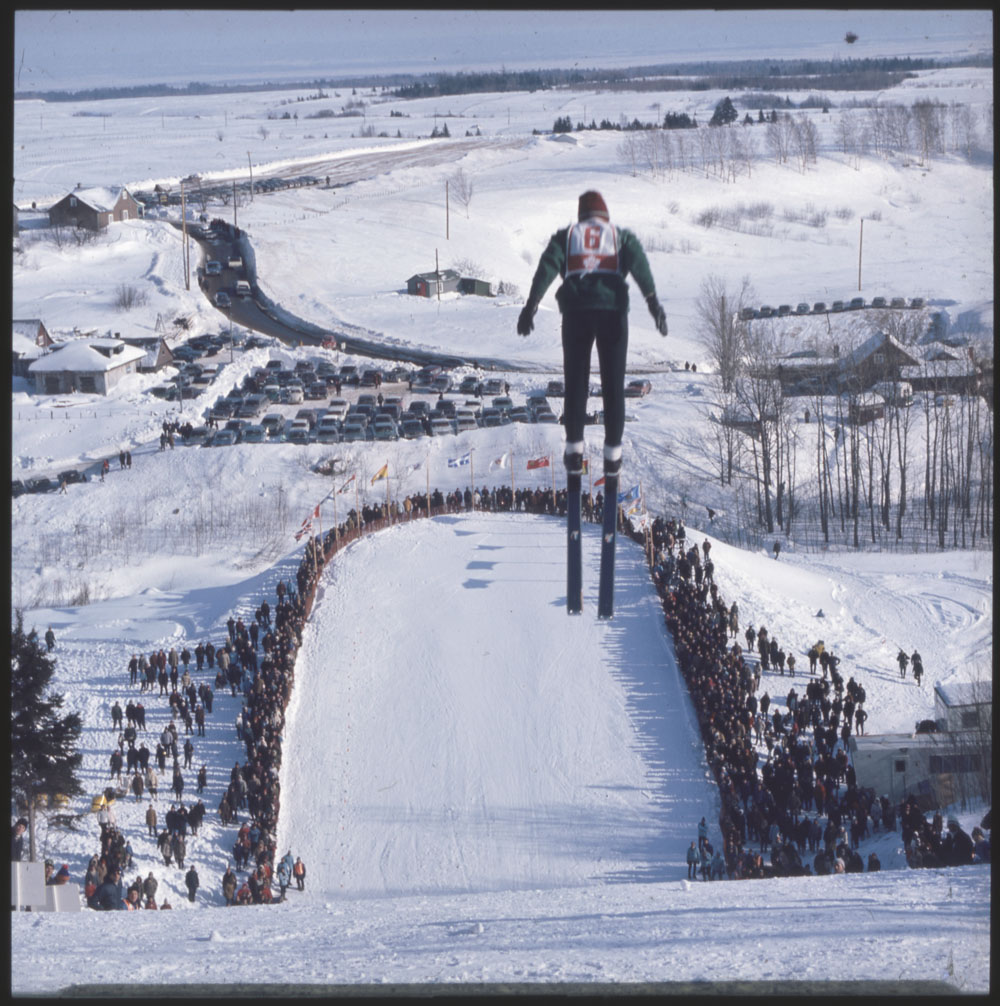 Ski Jumper mid-air with crowd below watching the first Canadian Winter Games at Québec City