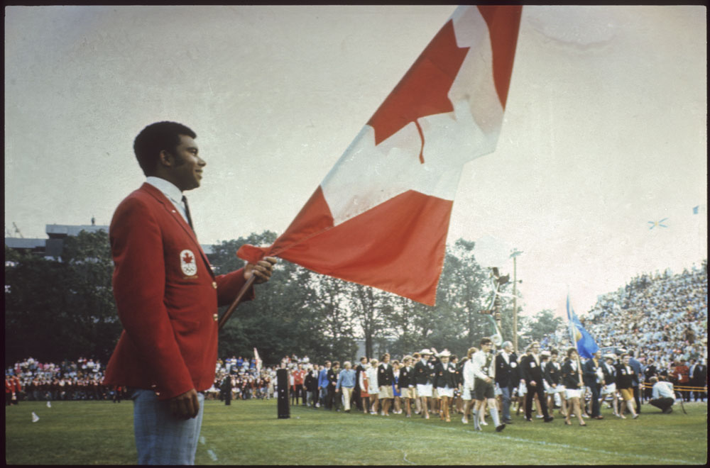 Harry Jerome holding the Canadian flag at the opening ceremonies of the first Canadian Summer Games at Halifax-Darmouth