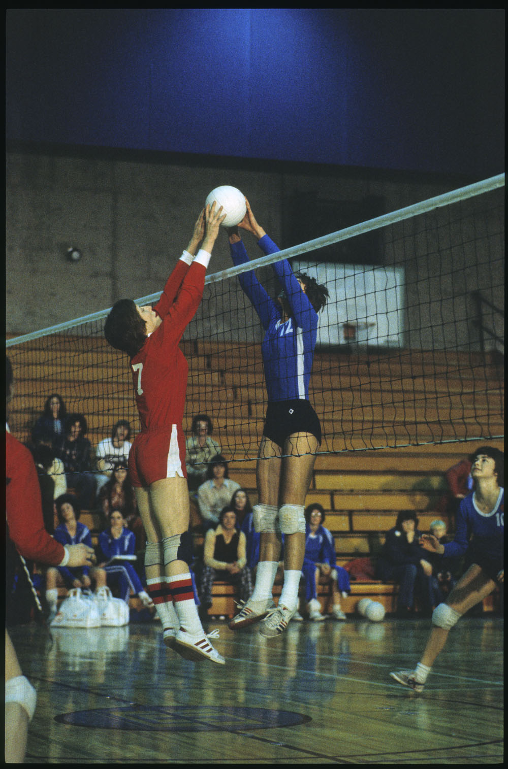 Two opposing female volleyball players jump for the ball above the net during the Third Canada Winter Games, at Lethbridge, Alberta