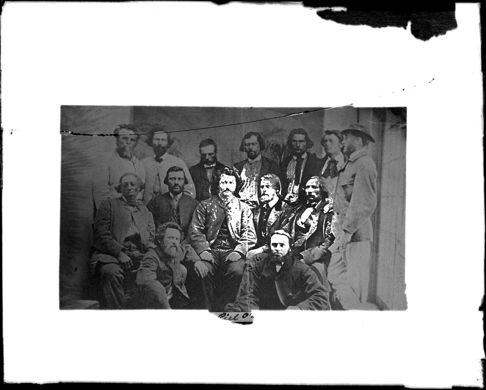 Black and white photograph of fourteen men seated and standing in three rows. There is a crack from the left side that runs across the top of the image.