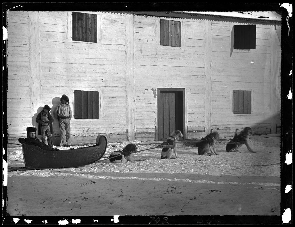 Man seated in a Métis cariole with four harnessed dogs and two men standing against a building in the background, Fort Garry, Northwest Territories now Winnipeg, Manitoba), 1871