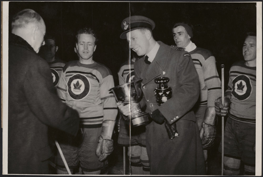 Photo of a man in uniform holding two trophies and smiling at another man. Behind them are members of a hockey team.