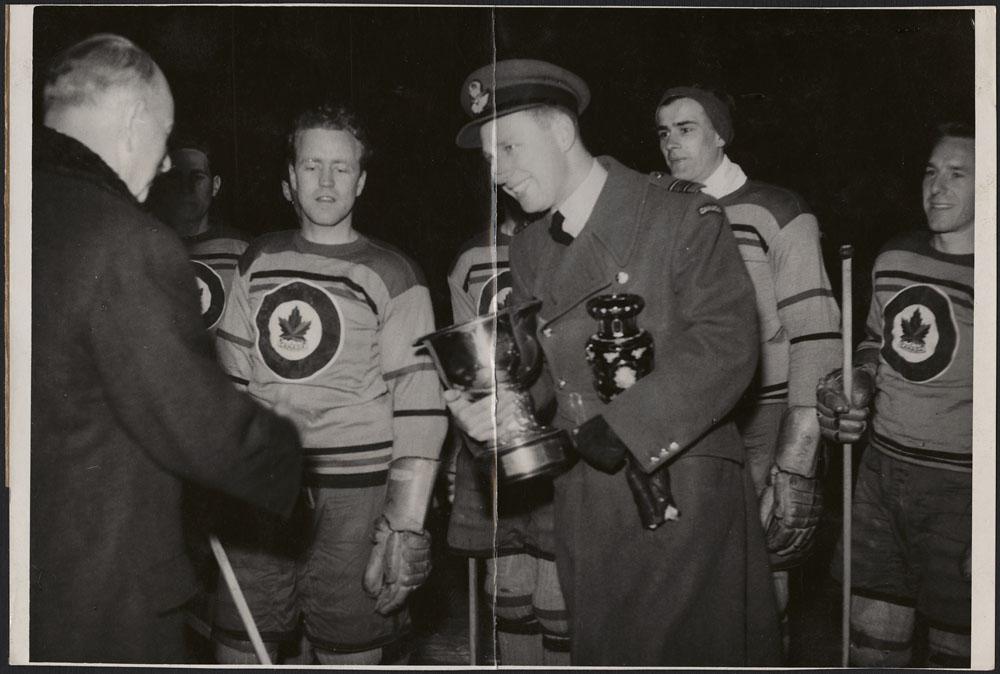 Photo d'un militaire en uniforme tenant deux trophées dans les mains et souriant à un autre homme. Les joueurs d'une équipe de hockey sont debout derrière eux.