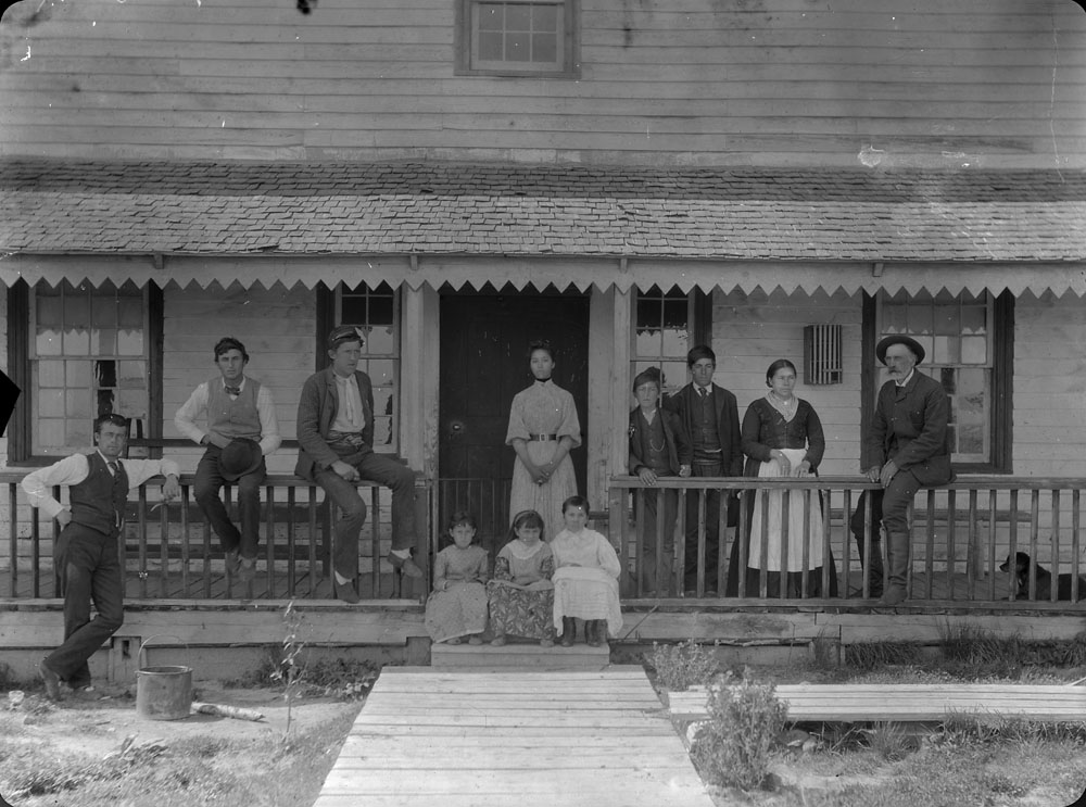 Black and white photograph of two women, four men, two young boys and three girls pose standing, leaning and sitting  on the front porch of a home.
