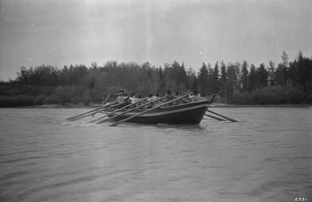 Black and white photograph of a long wooden boat being rowed by about ten men facing away from the camera and towards a line of trees in the background of the photograph.